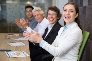 Cheerful multiethnic business people sitting at meeting in boardroom, clapping, looking at camera and laughing. Young woman sitting in front